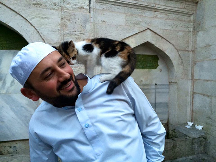 L'Imam Mustafa Efe con uno dei gatti che popolano la sua moschea.