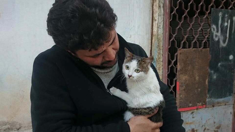 """Mohammad Alaa Aljaleel insieme ad uno dei gatti del rifugio """"Casa dei gatti Ernesto""""."""