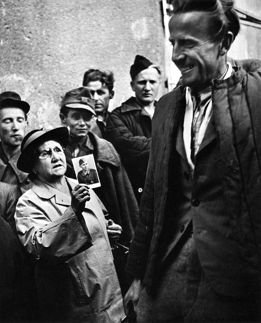 Una madre mostra la foto del proprio figlio ad un reduce di guerra, 1947. Foto di Ernst Haas.