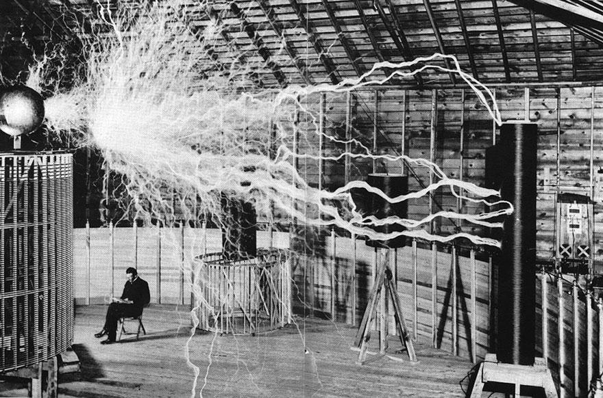 """Nikola Tesla seduto nel suo laboratorio con il suo """"magnifico trasmettitore""""."""