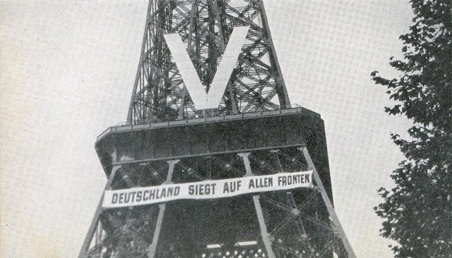 """La Torre Eiffel durante l'occupazione nazista. Così recita la scritta: """"La Germania vincerà su tutti i fronti"""", 1940."""