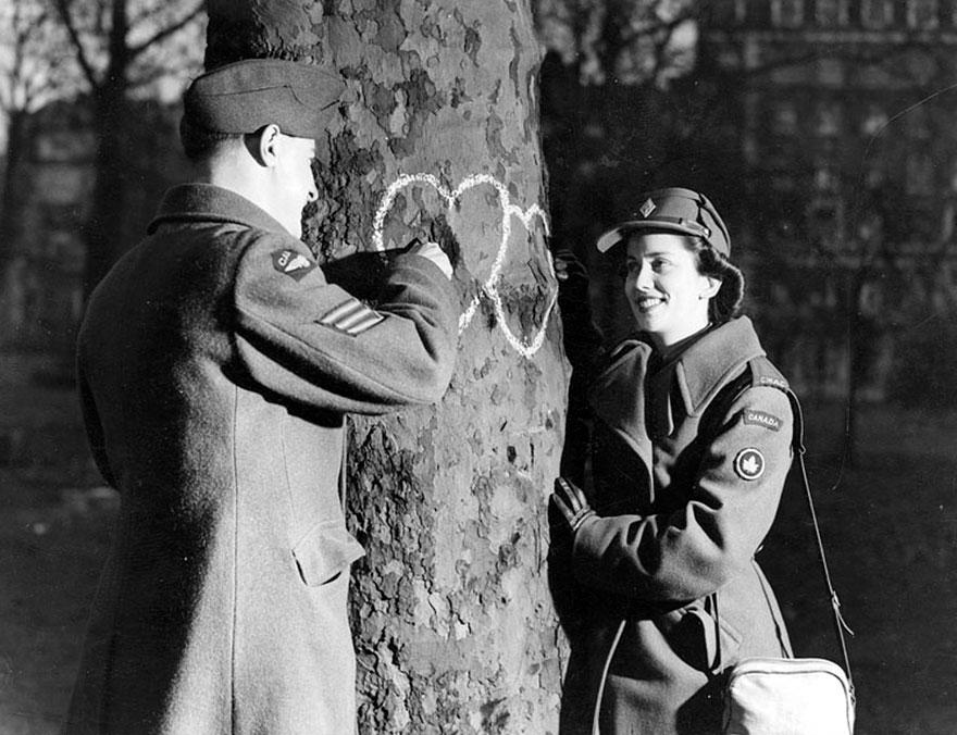 Giovane coppia disegna con il gessetto dei cuori su un albero. Giorno di San Valentino, 1944. Galt Museum & Archives