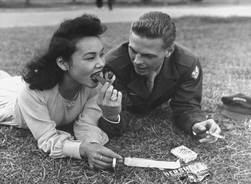 Soldato statunitense e ragazza del luogo dividono una barretta di cioccolata e le sigarette. Anni '40. John Florea