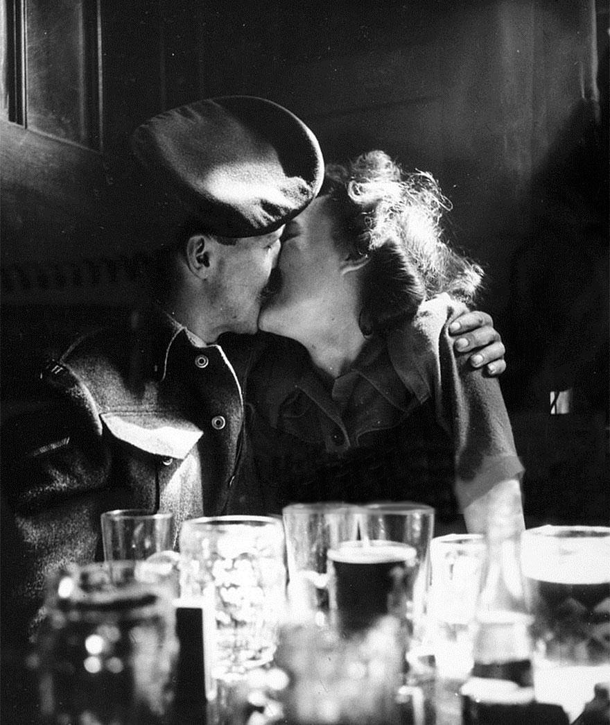 Una coppia che si bacia in un pub mostra come l'Europa festeggia la fine della Seconda Guerra Mondiale. Londra, 1945. Popperfoto.