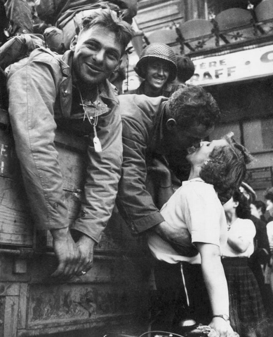 Soldato americano si sporge da un camion militare per baciare una donna francese durante la Liberazione di Parigi, 1944. Hulton Archive