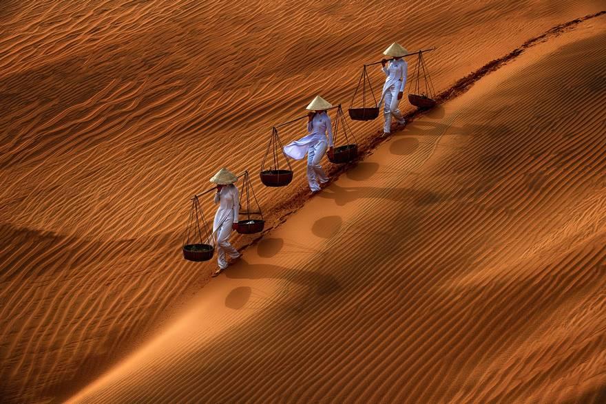 """""""Outlines And Shadows"""" di Danny Yen Sin Wong. Sulle dune di sabbia di Mui Ne, situato vicino alla sua città omonima nel Vietnam del Sud, tre ragazze camminano lungo il pendio indossando i loro tipici cappelli a cono e portando le loro bilance. Particolarmente suggestiva la creazione di linee e di effetti ombra sulla sabbia."""