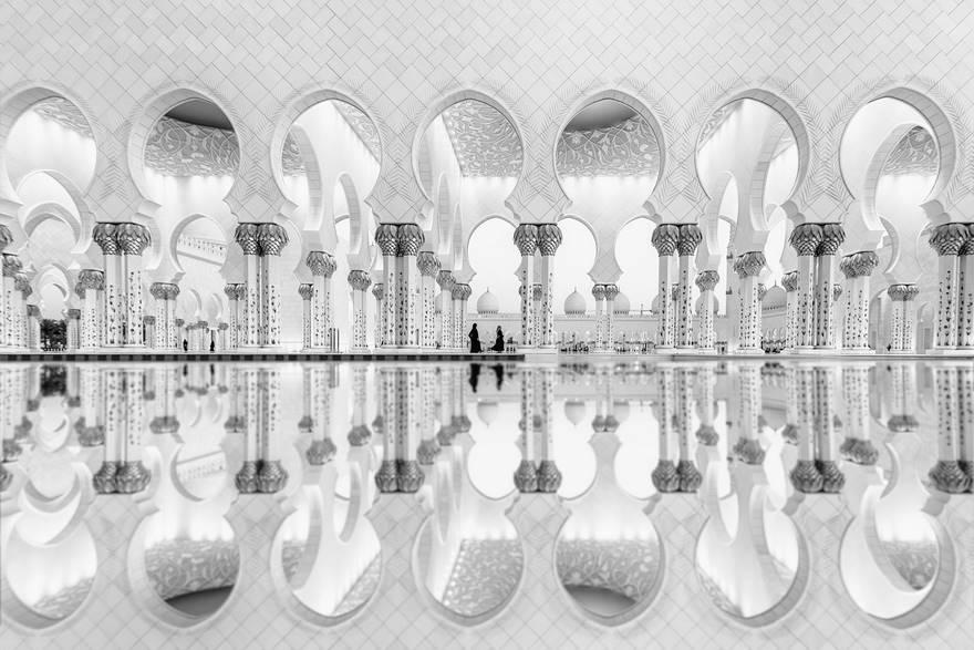 """""""Women Reflection"""" di Ali Al Hajri. Due donne che camminano riflettono le loro immagini in acqua, mettendo così in risalto la geometria architettonica della Grande Moschea di Sheikh Zayed."""
