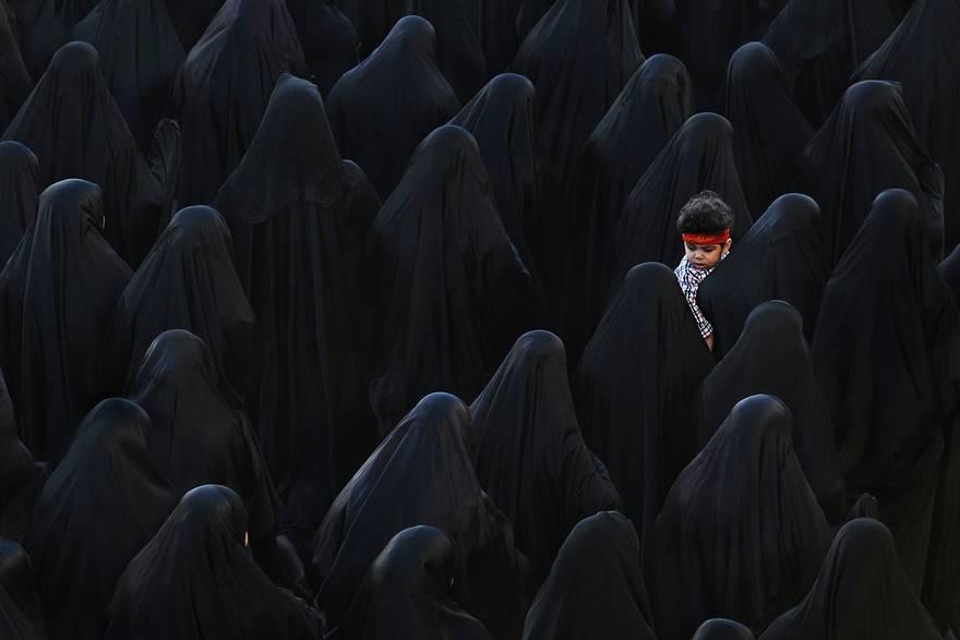 """""""Central Black"""" di Isa Ebrahim. Una donna musulmana del Bahrain porta in braccio suo figlio mentre partecipa ai funerali di Isa Radhi, il contestatore del Bahrain che sarebbe stato ucciso durante l'introduzione della legge marziale a Sitra, nel Manama meridionale, il 22 marzo del 2011."""