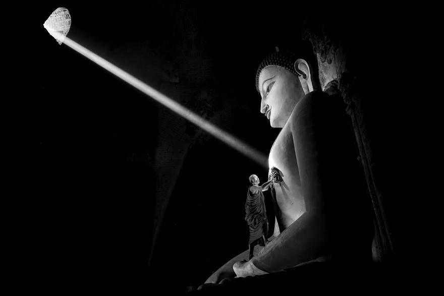 """""""I'm nothing"""" di Gunarto Gunawan. L'immagine è stata scattata in uno dei templi di Bagan nel Myanmar. Cattura un momento molto speciale: un raggio di sole entra attraverso una piccola finestra e colpisce il cuore della statua, mentre un monaco la sta pulendo."""