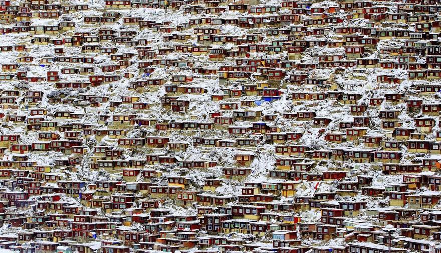 """""""Living Place"""" di Qingjun Rong. L'Istituto Tibetano Buddista Seda si trova a LaRong Ditch, nella Contea di Seda situata nel Ganzi, provincia di Sichuan. Dopo un'intensa nevicata durante la notte, la mattina seguente le case rosse dei monaci e delle suore sono tutte coperte di neve."""