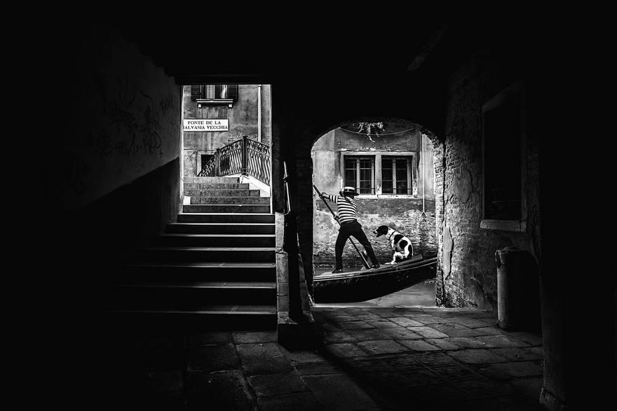 """""""Gondoliere"""" di Giuseppe Antonio Valletta. Questa foto è stata scattata accanto al Ponte della Malvasia Vecchia, a Venezia, uno dei luoghi più fotografati al mondo e dove è ancora possibile trovare momenti unici da immortalare. L'autore ha fotografato questo gondoliere, verso la fine di una dura giornata di lavoro, mentre stava tornando a casa con il suo cane."""