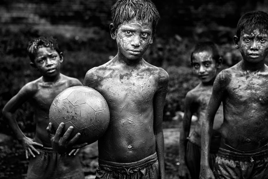 """""""Childhood"""" di Probal Rashid. Bambini dei quartieri poveri giocano a calcio in un campo fangoso nel distretto di Gazipur a Dhaka. Anche se la squadra di calcio del Bangladesh è posizionata al 162° posto, il paese ha milioni di appassionati di calcio, la maggior parte dei quali sostiene la propria squadra nazionale."""