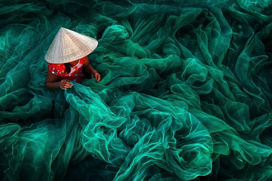 """""""Phan Rang Fishing Net Making"""" di Danny Yen Sin Wong. In un piccolo villaggio nel sud del Vietnam, vicino Phan Rang, una donna che indossa un tipico cappello a forma di cono è intenda a creare una rete da pesca usando il modo tradizionale vietnamita. La produzione di reti a mano è ancora una tipica attività vietnamita per le donne che la esercitano mentre i loro mariti vanno a pescare."""