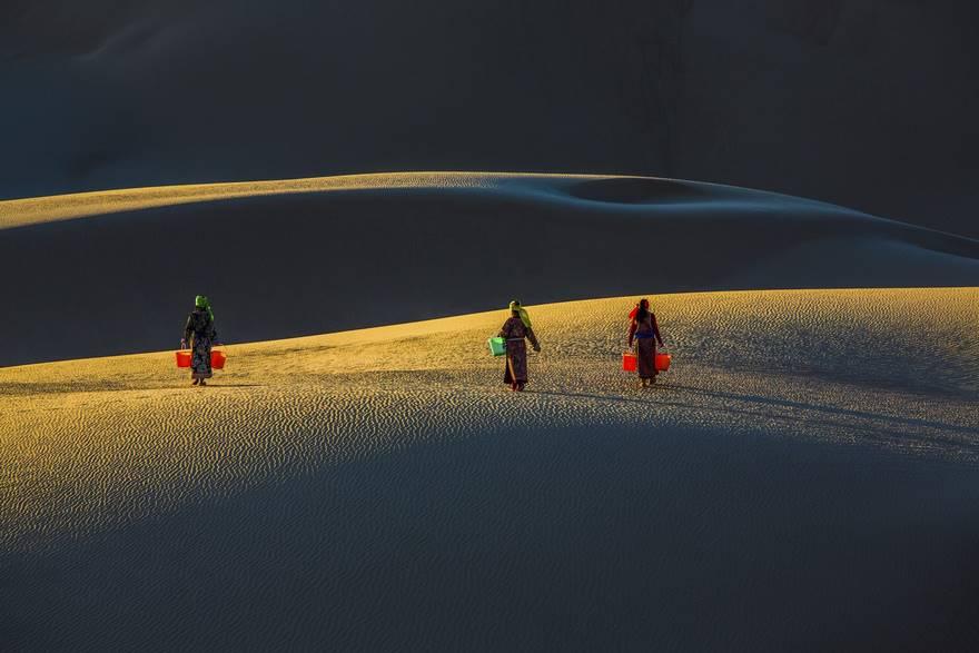 """""""Sisters In Desert"""" di Yushan Li. Mentre l'alba brilla sulla sabbia, nel deserto di Naima alcune ragazze mongole s'incamminano con dei secchi in mano per prendere l'acqua. Le loro ombre sono di rara bellezza."""