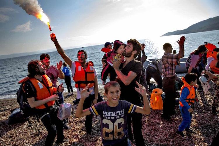"""""""Refugee Stream"""" di Jacob Ehrbahn. Il fotoreporter danese ha vinto la categoria """"Storyboard"""" con questa immagine commovente di rifugiati siriani e afgani sbarcati sull'isola greca di Lesbo. Dopo un arduo viaggio, Ehrbahn cattura la loro gioia e il sollievo per essere arrivati sani e salvi a destinazione."""
